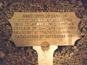 Engraved stone board in the Paris catacombs surrounded by bones and skulls.