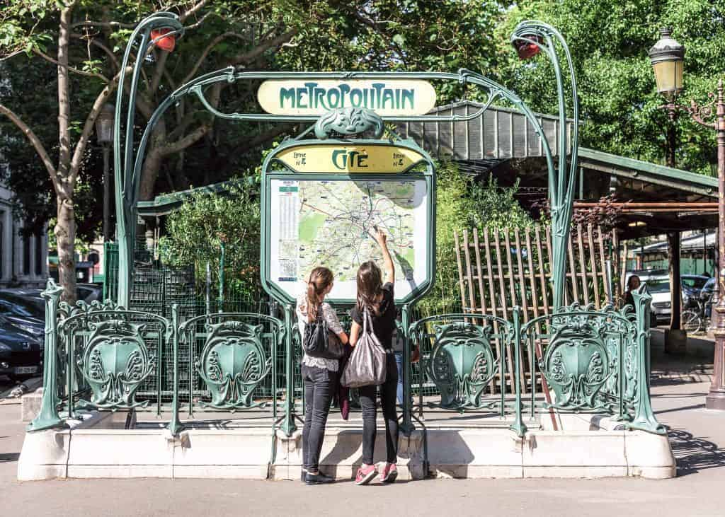 Young tourists in Paris, using map and looking for the direction at the entrance to the Paris Metropolitain (subway) at the Cite metro station.