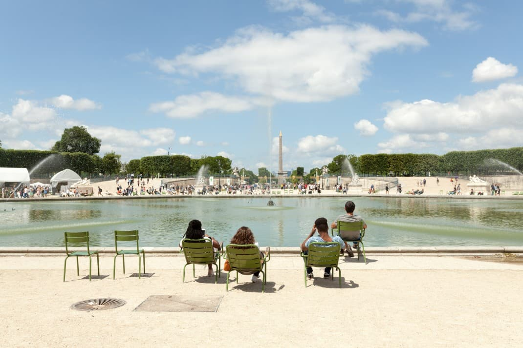 Tuileries garden fountains view with Parisians resting on chairs