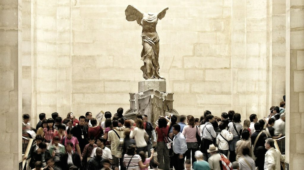 Visiting the Louvre - Tourists visiting The Louvre witness this iconic view of Samothrace's statue