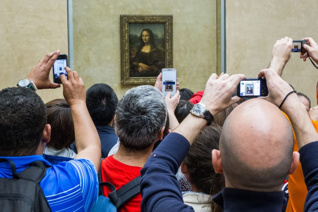 View of Mona Lisa paintings with a crowds of tourists taking photos while visiting The Louvre