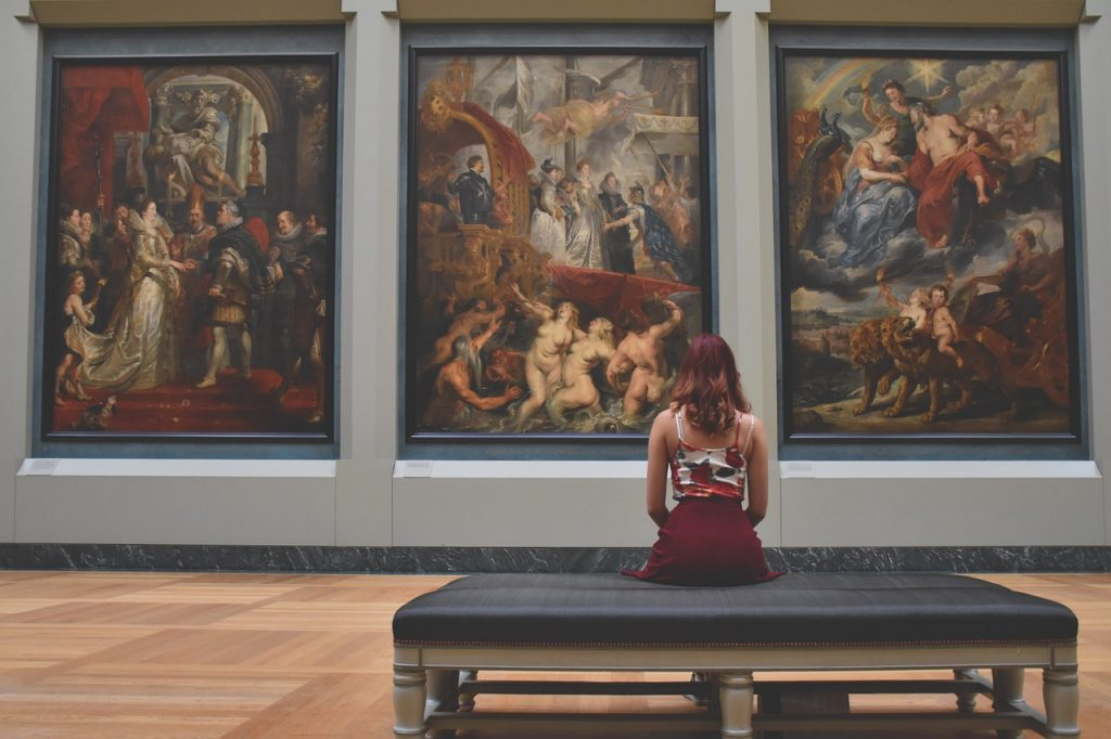 Woman sitting in front of classical paintings while visiting the Louvre museum