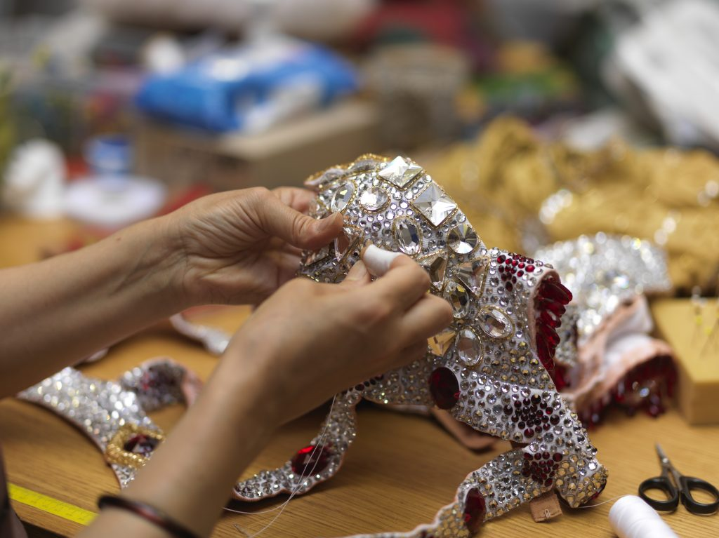 French artisans hand-crafting costumes of the Féerie show at the Moulin Rouge